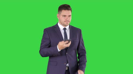 news stand : Thoughtful young businessman in suit and tie making several calls quickly on a Green Screen, Chroma Key.