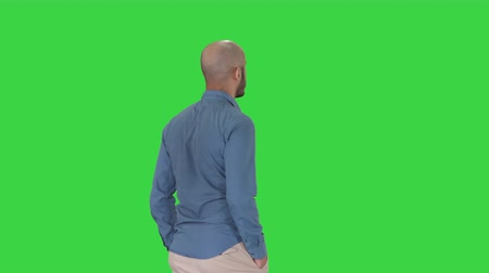 zadní : Casual young man walking on a Green Screen, Chroma Key.