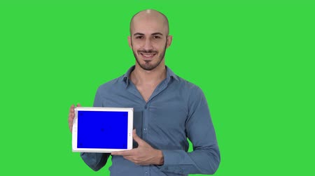 tab : Smiling casual man presenting a tablet with a blank screen on a Green Screen, Chroma Key. Stock Footage