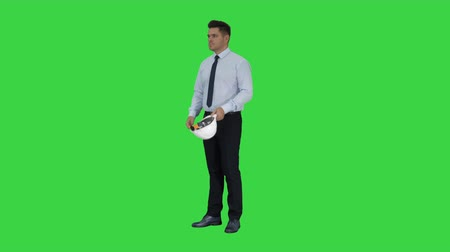 construtor : Businessman putting hardhat helmet on Safety on a Green Screen, Chroma Key.