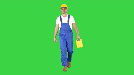 roadwork : Construction worker in hard hat holding plastic canister and walking on a Green Screen, Chroma Key. Stock Footage