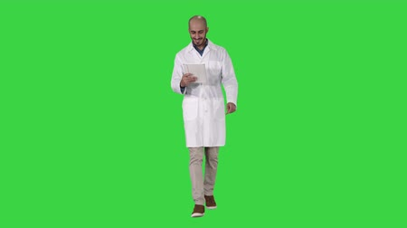 use computer : Mature male doctor holding digital tablet using it and walking on a Green Screen, Chroma Key.