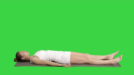 felvilágosodás : Yoga meditation laying on a mat with closed eyes on a Green Screen, Chroma Key.