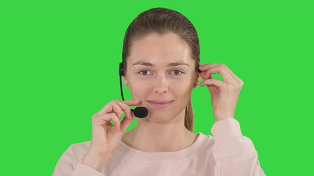 телефон доверия : Pretty female support center operator with headset smiling to camera on a Green Screen, Chroma Key.