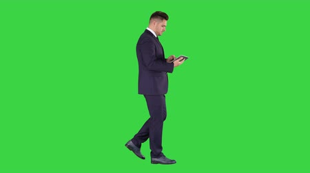 move well : Elegant young businessman using his PC tablet while walking on a Green Screen, Chroma Key. Stock Footage