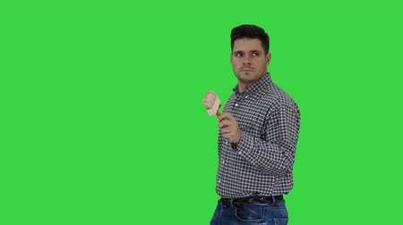 klucz : Painter man walking and pointing with brush on what he wants to paint on a Green Screen, Chroma Key.