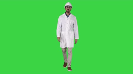 manipulacja : Young engineer in robe and helmet putting glasses on while walking on a Green Screen, Chroma Key. Wideo