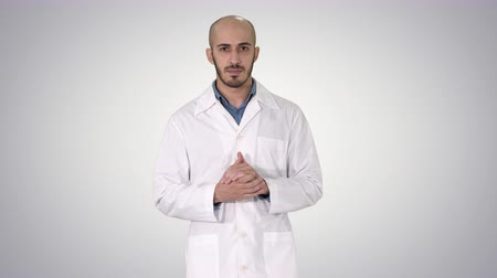 exibindo : Middle age doctor man wearing medical uniform presenting and pointing with palm of hand looking at the camera on gradient background. Stock Footage