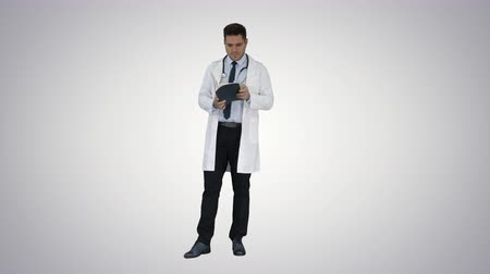 описание : Doctor reading Medical Report of Patient or Recepie or Text book on gradient background.