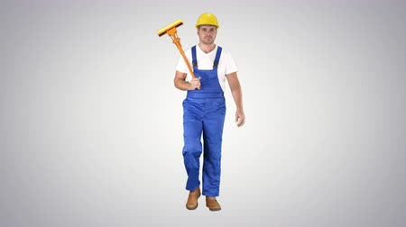 power equipment : Housecleaner in helmet walking with a mop on gradient background.