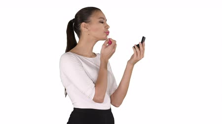 gracefully : Beautiful woman, dyes her lips lipstick pink, looking in the mirror on white background.