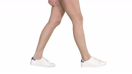 human foot : Women feet wearing white sneaker shoes walking on white background. Stock Footage