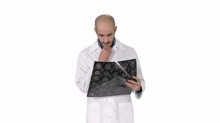 medical scan : Arabian physician reviewing a MRI brain scan while walking on white background.