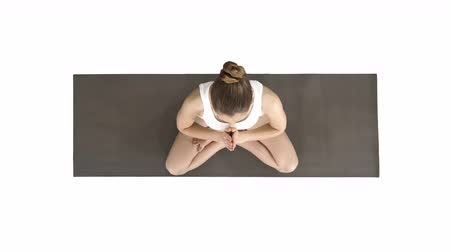 contemplação : Young yogi woman practicing yoga, making namaste gesture in lotus pose, wearing white t-shirt on white background. Vídeos