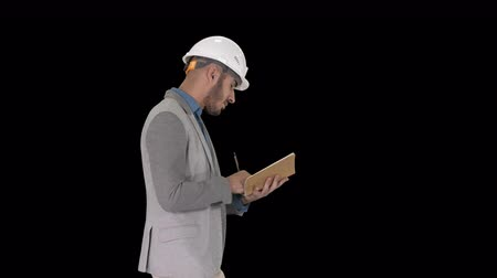 inspecionar : Arabic man in casual clothes and hard hat writing down checklist, Alpha Channel