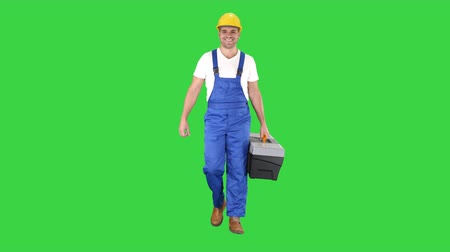 helpful : Builder with tool case walking on a Green Screen, Chroma Key.