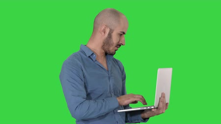 Young middle eastern businessman, standing and typing on laptop when holding it in his hands on a Green Screen, Chroma Key.