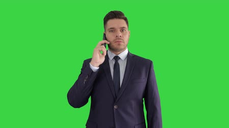 hívó : Businessman listening closely to caller on a Green Screen, Chroma Key.