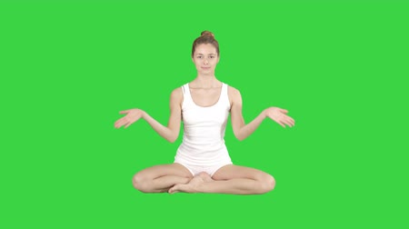 cross legged : Cute fitness woman exercising yoga sitting in lotus pose and smiling after that on a Green Screen, Chroma Key.