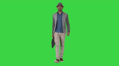 relance : Casual arabian man walking in a hat and with a briefcase on a Green Screen, Chroma Key.