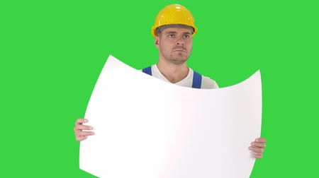 Thoughtful builder in helmet looking at blueprint and walking on a Green Screen, Chroma Key. 影像素材