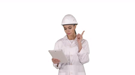 kolektor : Woman engineer checking information and objects on her tablet on white background. Dostupné videozáznamy