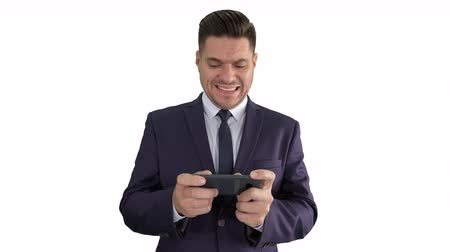Funny businessman playing in game on the phone and winning on white background.