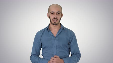 продвигать : Arabic young man in shirt talking presenting something and pointing to the side on gradient background. Стоковые видеозаписи