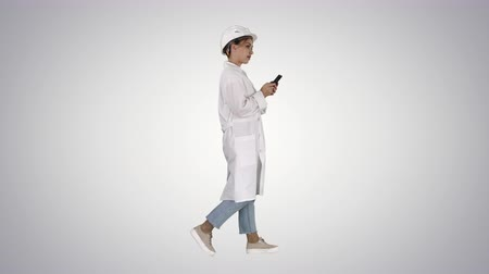 examination room : Female Scientist Using Smartphone Walking on gradient background.
