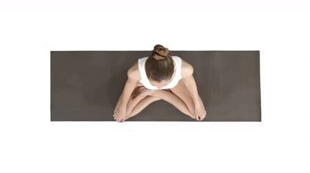 restorative : Young sporty woman practicing yoga sitting in lotus pose and breathing deeply on white background.