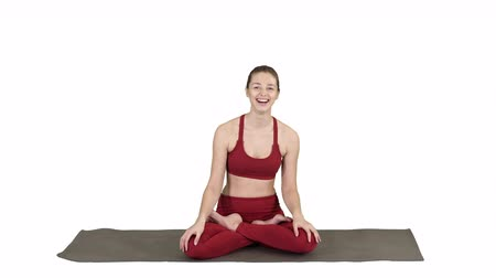 álmodozó : Beautiful woman sitting on yoga mat and talking to someone on white background.