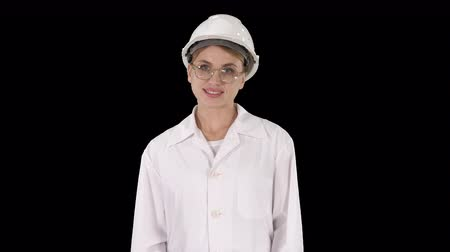 realization : Professional woman in lab coat and white hardhat walking and smiling, Alpha Channel