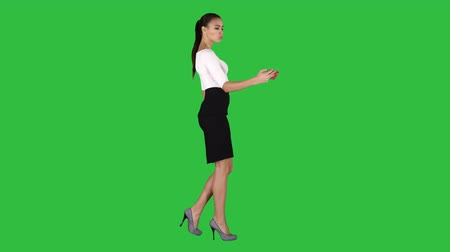 tela : Young brunette taking selfie photo on smartphone smiling joyful and walking on a Green Screen, Chroma Key.
