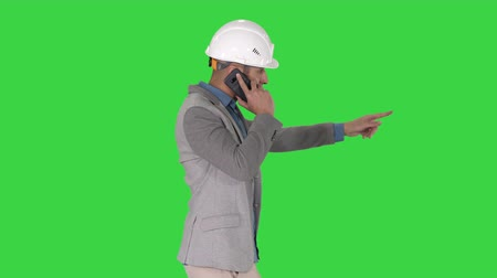klagen : Architect engineer makes a phone call complaining about the results of work Pointing to the objects in front on a Green Screen, Chroma Key.