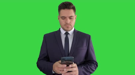 phone call screen : Serious businessman texting message on his phone on a Green Screen, Chroma Key.