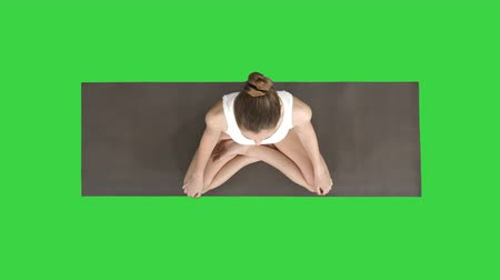 restorative : Young sporty woman practicing yoga sitting in lotus pose and breathing deeply on a Green Screen, Chroma Key. Stock Footage
