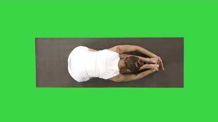 shiva : Young blond attractive woman practicing yoga, doing Seated forward bend exercise, paschimottanasana pose on a Green Screen, Chroma Key.