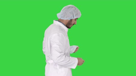 опытный : Arabic doctor walking and putting medical cap on on a Green Screen, Chroma Key. Стоковые видеозаписи