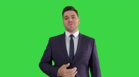 exibindo : Business man pointing on product and talking to camera on a Green Screen, Chroma Key.