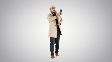 щетина : Cheerful man in coat taking photo making selfie on gradient background.