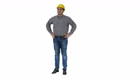 hand on chin : Smiling construction worker in yellow helmet looking at perfect well built object Hands on hips on white background. Stock Footage