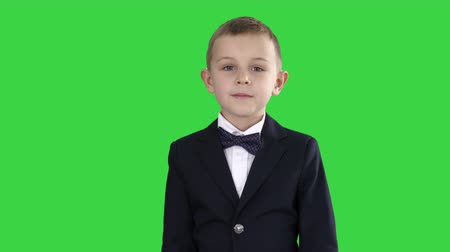 jovial : Little boy in a costume with a bow tie walking on a Green Screen, Chroma Key.