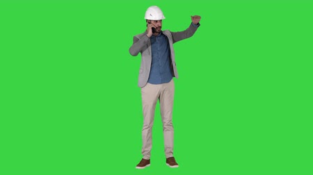 tela : Engineer talking a mobile phone inspecting construction work of crane on a Green Screen, Chroma Key.