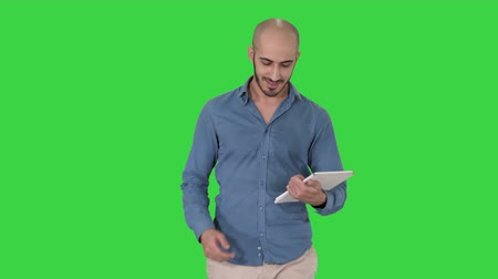 news stand : Arab presenter walking with digital tablet swiping pages on it on a Green Screen, Chroma Key.