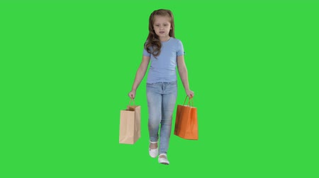 гласность : Little girl with shopping bags walking on a Green Screen, Chroma Key. Стоковые видеозаписи