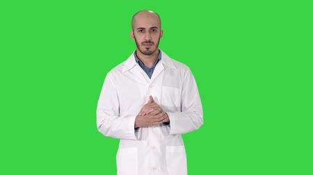 exibindo : Middle age doctor man wearing medical uniform presenting and pointing with palm of hand looking at the camera on a Green Screen, Chroma Key. Stock Footage