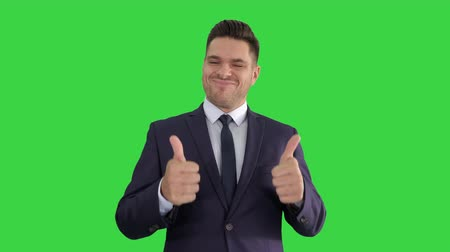 competence : Happy business man holding thumbs up on a Green Screen, Chroma Key. Stock Footage