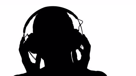 wearing earphones : Silhouette Charming woman smiling while listening to music in headphones.
