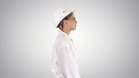 físico : Scientist physicist woman walking in lab coat and hardhat on gradient background.
