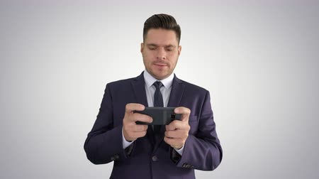 kaybediyor : Handsome businessman playing with his smartphone and losing on gradient background.